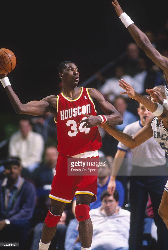 UNDATED: Houston Rockets' Hakeem Olajuwon #34 looks to pass during a game. NOTE TO USER: User expressly acknowledges and agrees that, by downloading and or using this photograph, User is consenting to the terms and conditions of the Getty Images License Agreement. (Photo by Focus on Sport/Getty Images) *** Local Caption *** Hakeem Olajuwon